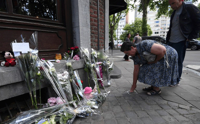 Bernadette Hennart (C), the mother of killed policewoman Soraya Belkacemi, flanked by Soraya's brother Kamel Belkacemi (R), touches a chalk circle drawn by Belgian police to mark the presence of bullet casing on the crime scene, as she pays tribute to her daughter, on 30 May, 2018, in Liege at a makeshift altar situated where the two policewomen were killed during an attack the day before. Picture: AFP.