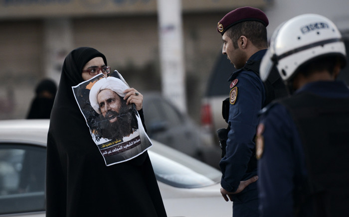 A Bahraini woman holds a poster of prominent Shiite Muslim cleric Nimr al-Nimr during clashes with riot police following a protest against the execution Nimr of by Saudi authorities, in the village of Daih, west of the capital Manama on 4 January, 2016. Picture: AFP.