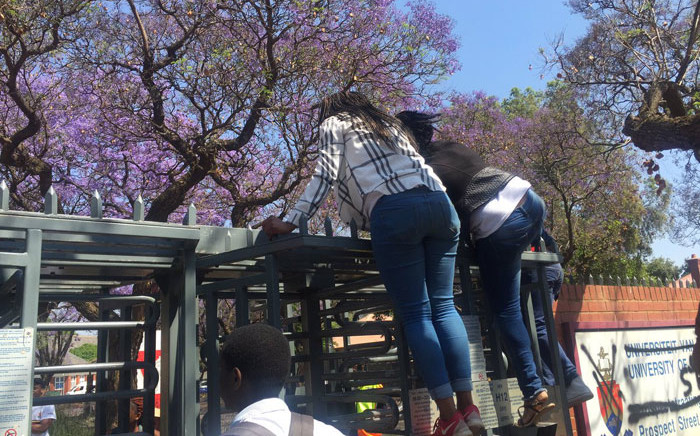 UP students assist each other to jump over turnstile gates to gain entry to the campus. Picture: Dineo Bendile/EWN
