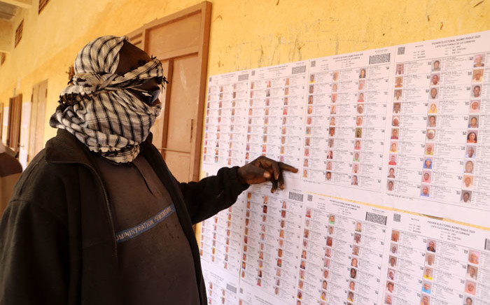 A voter wearing a scarf to cover his face checks the voter's roll at a polling station during the parliamentary elections in Gao, Mali, on 29 March 2020. Picture: AFP