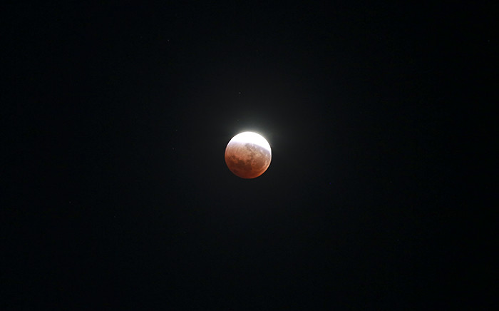 For the first time in 33 years, the moon, earth and sun aligned to present a large, swollen moon being eclipsed and painted a rusty red by our planet's shadow. Picture: Thomas Holder/EWN
