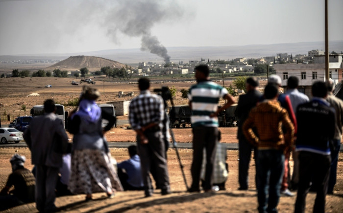 FILE: Smoke rises from the Syrian town of Kobani, seen from near the Mursitpinar border crossing on the Turkish-Syrian border in the southeastern town of Suruc, Sanliurfa province, on 3 October, 2014. Picture: AFP.