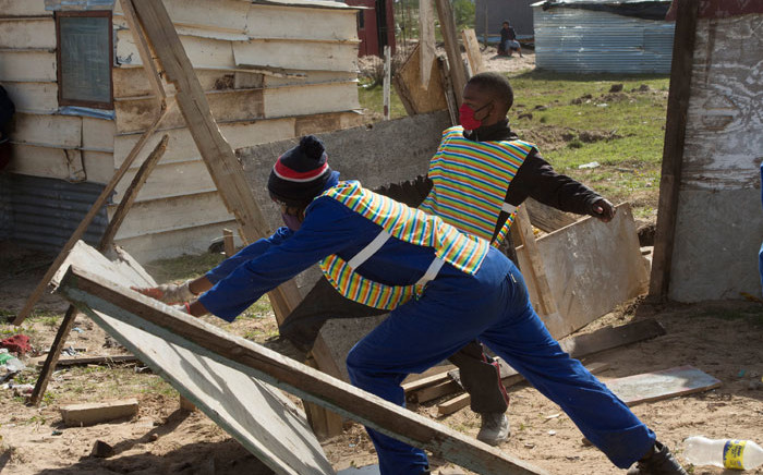 Workers, protected by members of the Cape Town Metro Police and South African Police Services, break down uninhabited shacks in Bloekombos, Kraaifontein, in Cape Town on 6 August 2020. Picture: AFP