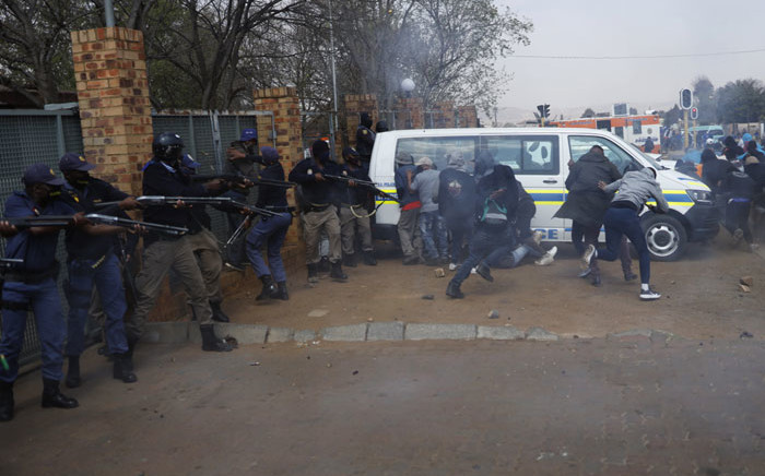 South African Police Service (SAPS) officers fire rubber bullets at protesters outside the SAPS offices in Eldorado Park, near Johannesburg, on 27 August 2020, during a protest by community members after a 16-year-old boy was allegedly shot dead by a policeman. Picture: AFP