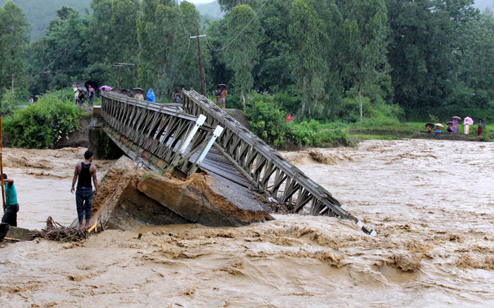 FILE: People look at the bridge which was washed away by the floodwaters in Thoubal District in Manipur state on 1 August, 2015. At least 21 people were killed in a landslide caused by heavy rains in Manipur's Chandel district, said police. Picture: AFP.