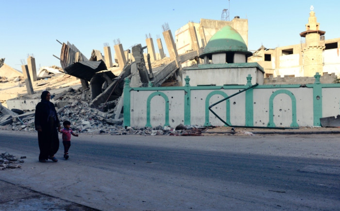 A Palestinian woman and a child walk past the destroyed Omari mosque on 12 August 2014 in Jabalia, northern Gaza Strip. Picture: AFP.