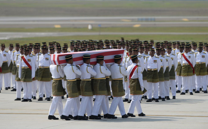 Soldiers carry a coffin with the remains of a Malaysian victim from the Malaysia Airlines flight MH17 that crashed in Ukraine during a ceremony at the Bunga Raya complex at Kuala Lumpur International Airport in Sepang on 22 August, 2014. Picture: AFP.