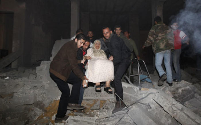 Palestinian men evacuate an elderly woman following an Israeli air strike on November 14, 2012 in Gaza City. Picture: AFP.