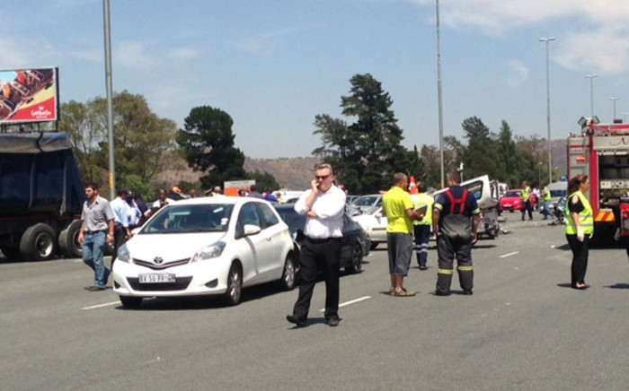Emergency vehicles and people stand on the scene of a horrific accident on the N12 East after a truck swept several cars after failing to stop on 14 October 2014. Picture: Vumani Mkhize/EWN.