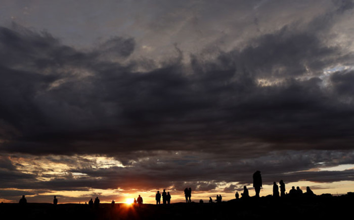 People watch from a hill during sunset after an US-led coalition airstrike on Kobani, Syria, as seen from the Turkish side of the border. Picture: EPA.