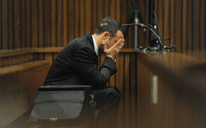 Oscar Pistorius holds his hand to his face while a witness recounts to the court the moments after the murder during the fourth day of his trial at the High Court in Pretoria on 6 March 2014. Picture: Pool.