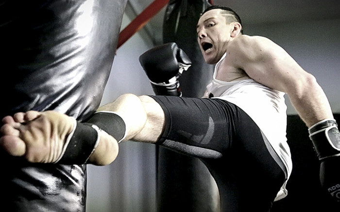 "Gideon ""Juggernaut"" Drotschie performs a roundhouse kick to the bag at Reps MMA gym in Bellville, Cape Town. Picture: Thomas Holder"