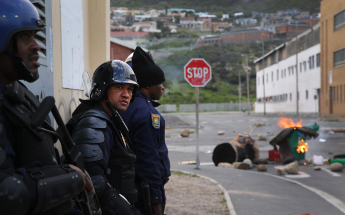 FILE: Police regroup behind a building before using rubber bullets to disperse angry protesters in Hangberg. Picture: EWN.