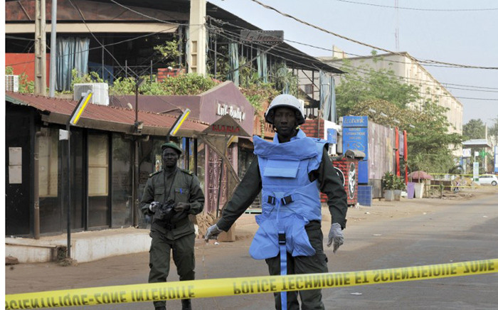 Policemen stand near the La Terrasse restaurant, as seen in the backround with the blue curtains, in Bamako on 7 March, 2015, after five people, including a French and a Belgian national, were shot dead overnight in the restaurant in a suspected terror attack. Picture: AFP.