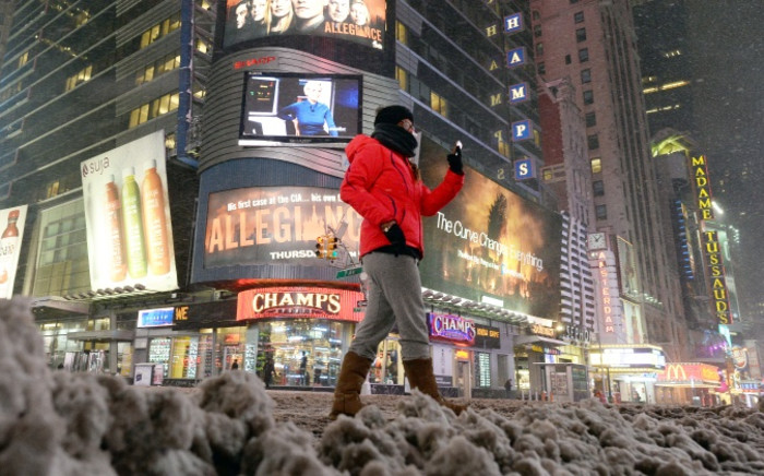 Few people walk on a deserted street in New York's Times Square during a snow storm on 26 January 2015. Picture: AFP.