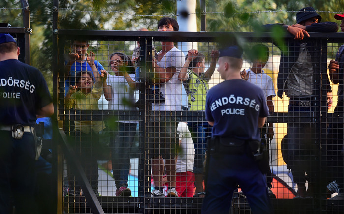 FILE: Police officers stand on guard in front of a metal gate at the closed M5 highway to block circulation of migrants at the Hungarian-Serbian border on 15 September, 2015. Picture: AFP.