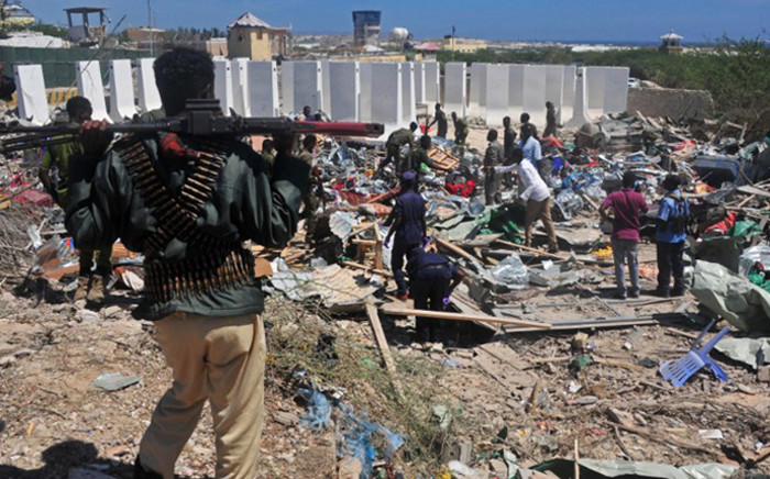 Civilians and soldiers stand amongst scattered objects and belongings at the scene of a car bomb attack near the Peace Hotel of the capital Mogadishu, on 2 January, 2017. Picture: AFP.