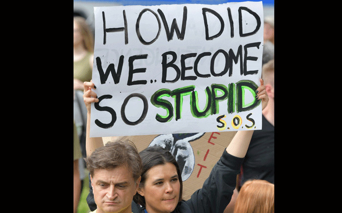 """A protester holds up a sign reading """"How did we become so stupid """" during a """"Fridays for Future"""" demonstration in Berlin to protest for climate action in Berlin, on July 19, 2019. Launched by Swedish activist Greta Thunberg, """"Fridays for Future"""" has seen pupils """"strike"""" against school teaching each Friday for months across Europe. Picture: AFP."""