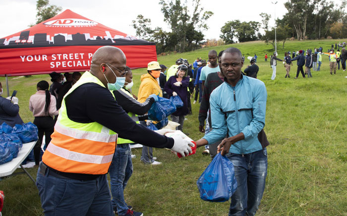 Johannesburg Environmental and Infrastructure MMC Mpho Moerane hands over maize to a waste picker during a food hamper drive at Innes Free Park in Sandton. Picture: Ahmed Kajee/EWN