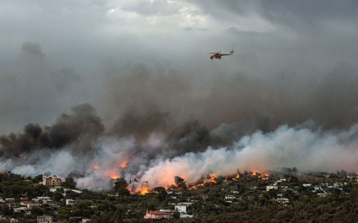 A firefighting helicopter flies over a wildfire raging in the town of Rafina near Athens, on 23 July 2018. Picture: AFP