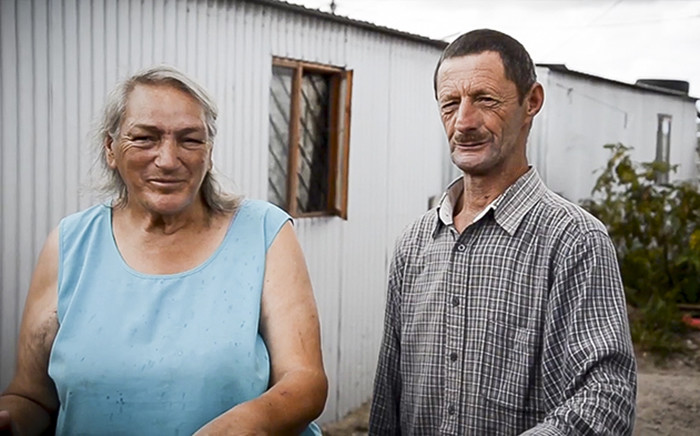 Two residents of Blikkiesdorp in Delft, Cape Town, stand outside one of the tin houses typical of the settlement. Picture: Kim Harrisberg/EWN