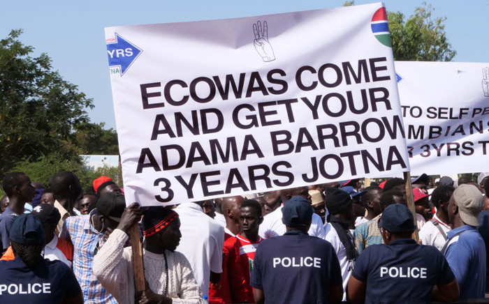 FILE: Protesters hold a banner as they take part in a demonstration against Gambian President, in Banjul, Gambia, on 16 December 2019. Picture: AFP