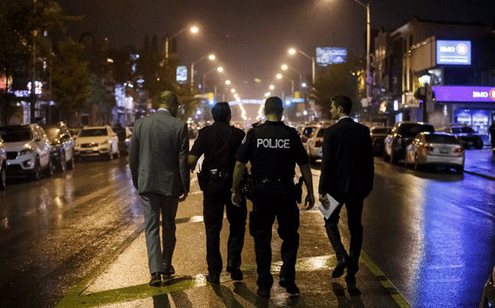 Toronto Police officers work on Danforth St., at the scene of a shooting in Toronto, Ontario, Canada on July 23, 2018. A gunman opened fire in central Toronto on Sunday night, injuring 13 people including a child. Two dead including gunman, police reported. Picture: AFP.
