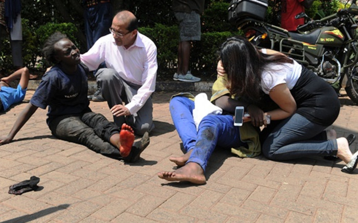 Injured people receive assistance from bypassers after masked gunmen stormed an upmarket Nairobi mall and sprayed gunfire on shoppers and staff on September 21, 2013 in Nairobi. Picture: AFP