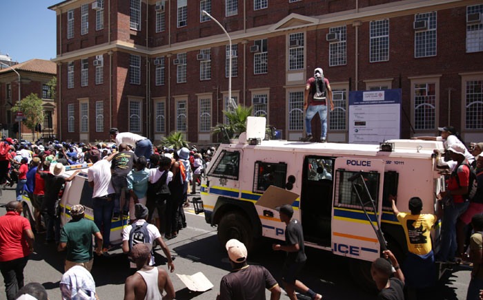 Fees 2017 protesters climb on top of the police Nyala on their way to Parliament. Picture: Anthony Molyneaux/EWN.