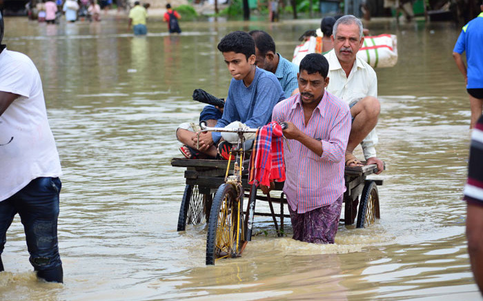 An Indian rickshaw puller transports commuters on a flooded street after a heavy downpour at Baldakhal village in Agartala, the capital of northeastern state of Tripura, on 14 July 2019. Picture: AFP