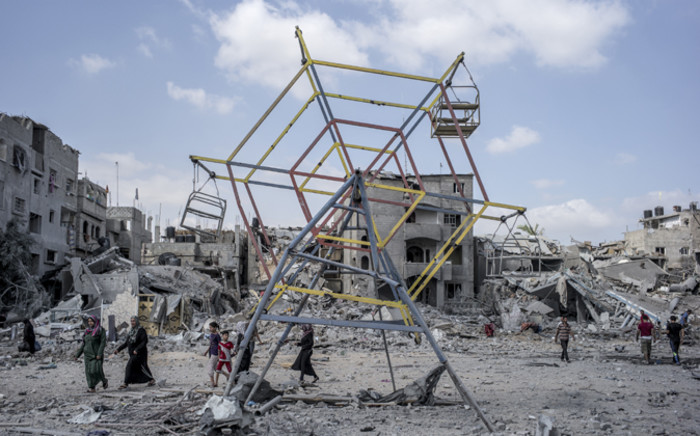 Palestininans go their way past rubbles and a mini ferris wheel in the northern district of Beit Hanun in the Gaza Strip, during an humanitarian truce, on 26 July 2014.
