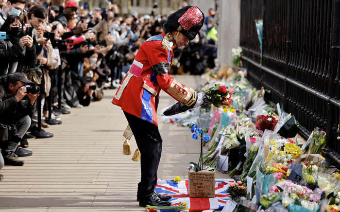 An ardent British royals fan lays a floral tribute at the front of Buckingham Palace in central London on 9 April 2021 after the announcement of the death of Britain's Prince Philip, Duke of Edinburgh. Picture: Tolga Akmen/AFP