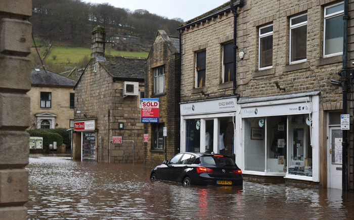 FILE: A car is seen submerged in floodwater in the streets of Hebden Bridge, northern England, on 9 February 2020, as Storm Ciara swept over the country. Picture: AFP.
