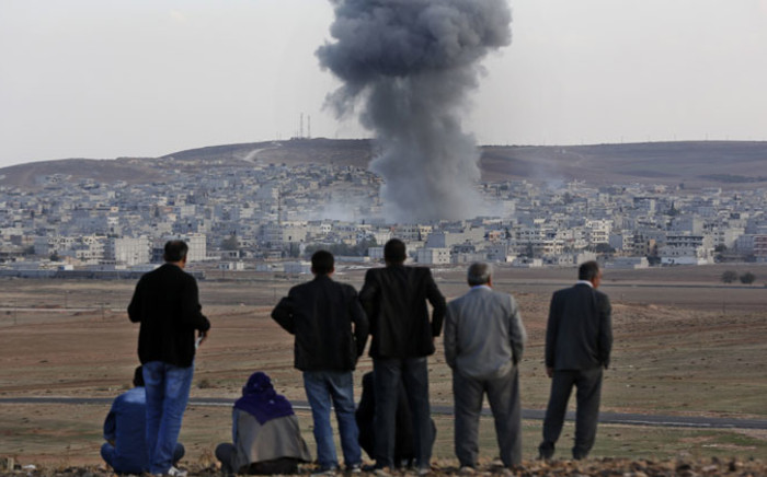 Local residents watch smoke from an explosion rising over the Syrian city of Kobani as they watch the apparent US-led coalition's airstrike against IS positions in the border region from a hillside on the Turkish side of the border near the Suruc district city of Sanliurfa, Turkey, on 22 October 2014. Picture: EPA.
