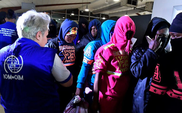 An International Organization for Migration (IOM) member stand next to Ivorian migrants returning from Libya to be repatriated in their country as they arrive at the airport of Abidjan on 20 November 2017. Picture: AFP.