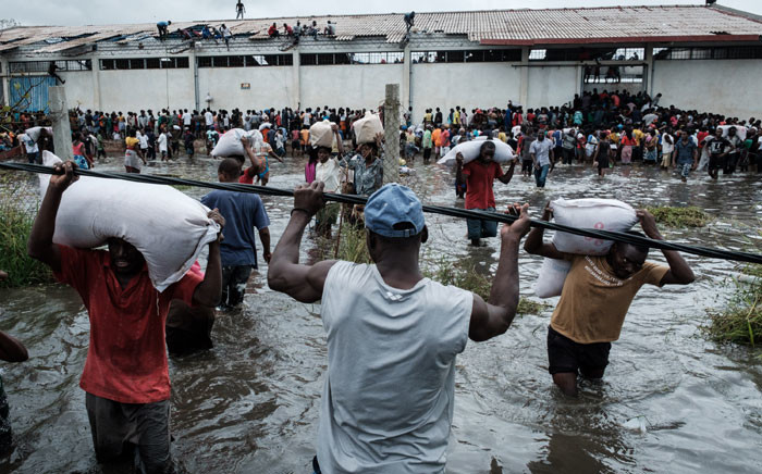 """People take part in the looting sacks of Chinese rice printed """"China Aid"""" from a warehouse which is surrounded by water after cyclone hit in Beira, Mozambique, on 20 March 2019. Picture: AFP"""