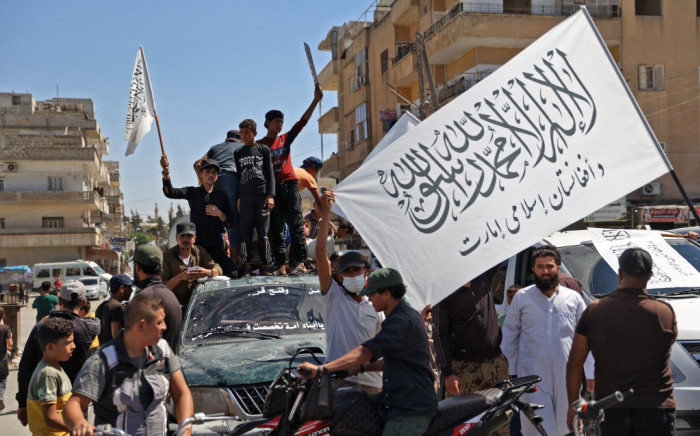 """Members of Syria's top jihadist group the Hayat Tahrir al-Sham (HTS) alliance, led by al-Qaeda's former Syria affiliate, parade with their flags and those of the Taliban's declared """"Islamic Emirate of Afghanistan"""" through the rebel-held northwestern city of Idlib on August 20, 2021. The armed group that formally broke ties with al-Qaeda years ago is considered to be the most prominent jihadist group in Syria after a decade of war. HTS controls nearly half of the Idlib region -- the last remaining opposition bastion in Syria -- alongside other less influential groups. OMAR HAJ KADOUR / AFP"""