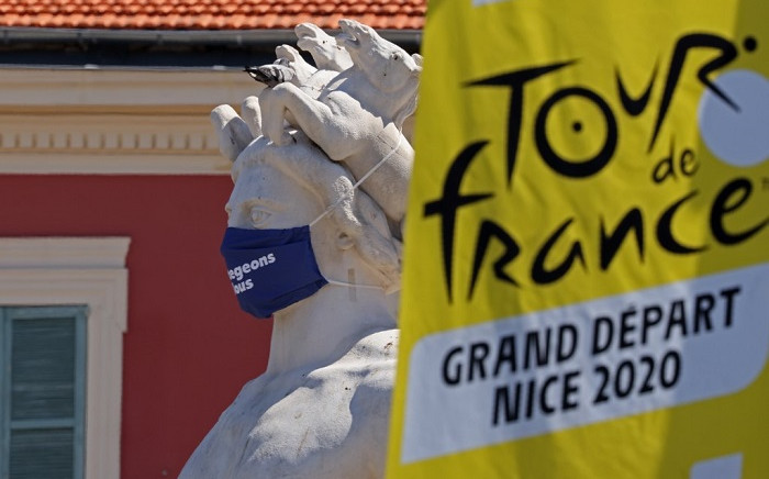 In this file photo taken on 26 August 2020 the logo of the 2020 Tour de France is seen next to a masked statue in the French Riviera city of Nice. Picture: AFP
