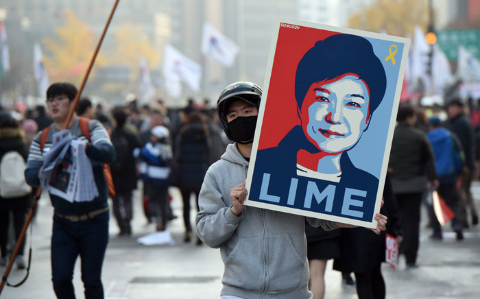A protester holds a placard showing a portrait of South Korea's President Park Geun-Hye during an anti-government rally in central Seoul on November 19, 2016. Tens of thousands of protestors gathered in Seoul on November 19 for the fourth in a weekly series of mass protests aimed at forcing President Park Geun-Hye to resign over a corruption scandal. Picture: AFP.