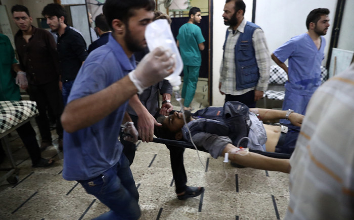 FILE: An injured Syrian man arrives on a stretcher to receive treatment at a makeshift hospital on 3 October 2016, following reported air strikes in the rebel-held town of Douma, on the eastern outskirts of the capital Damascus. Picture: AFP.