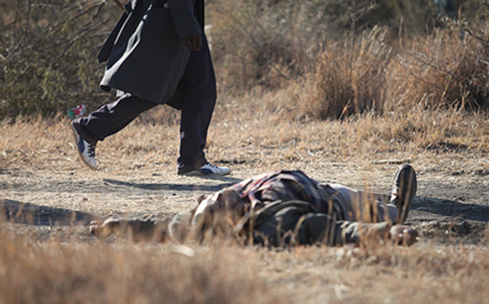 A man walks past a dead protester at Lonmin's Marikana mine on 14 August, 2012. Around 3000 drill operators down tools during a illegal strike. Picture: Taurai Maduna/Eyewitness News.