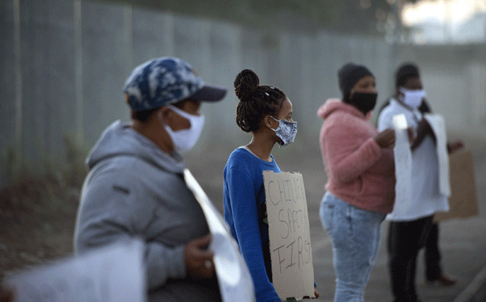 A small group of people take part in a protest outside a school in Bishop Lavis, to protest against the South African government's decision to open some schools, in Cape Town on June 1, 2020. South Africa moved into level three of a five-tier lockdown on June 1, 2020, to continue efforts to curb the spread of the COVID-19 coronavirus. Picture: AFP