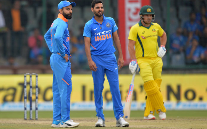 FILE: India's Virat Kohli (L) stands with bowler Bhuvneshwar Kumar (C) during the fifth one-day international (ODI) cricket match between India and Australia at the Feroz Shah Kotla Stadium in New Delhi on 13 March 2019. Picture: AFP