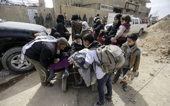 A Syrian man helps women sit on a push-cart during a civilian evacuation from the Eastern Ghouta enclave through the regime-controlled corridor in Hawsh al-Ashaari, east of the enclave town of Hamouria on the outskirts of the capital Damascus on 15 March 2018. Picture: AFP