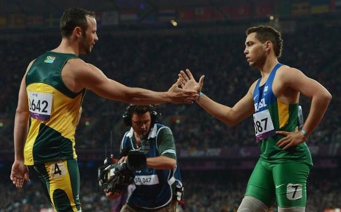 Alan Fonteles Cardoso Oliveira of Brazil is congratulated by Oscar Pistorius of South Africa after winning gold in the Men's 200m - T44 on Day 4 of the London Paralympics. Picture: London2012.com.