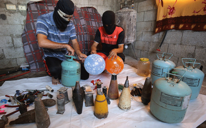 Masked Palestinians inflate balloons before attaching flammable objects to them to be flown toward Israel, in Rafah in the southern Gaza Strip, on 8 August 2020. Picture: AFP