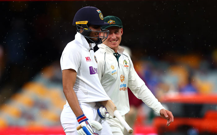 Australia's Marnus Labuschagne and India's batsman Shubman Gill walk off the field as rain stop the play during the day four of the fourth cricket Test match between Australia and India at The Gabba in Brisbane on 18 January 2021. Picture: AFP