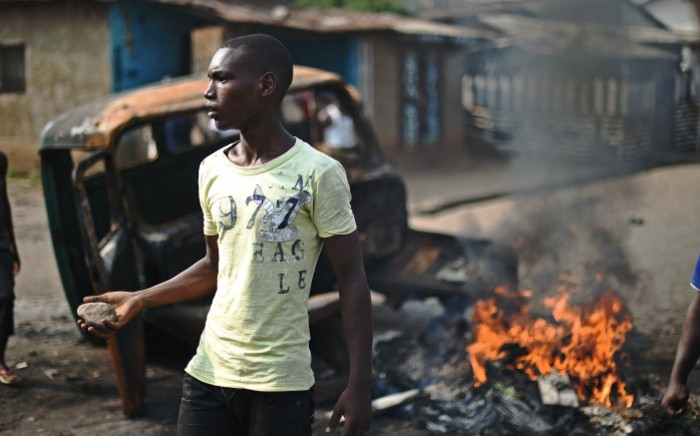 FILE: A protester opposed to Burundian President Pierre Nkurunziza's third term brandishes a rock as he stands beside a burning vehicle during a demonstration in the Buyenzi neighborhood of Bujumbura on 26 May, 2015. Picture: AFP.