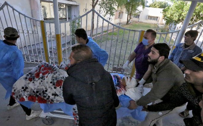 An injured man is rushed to a hospital following a twin suicide bombing on a bustling commercial street in the heart of the Iraqi capital Baghdad, on 21 January 2021. Picture: Sabah ARAR/AFP