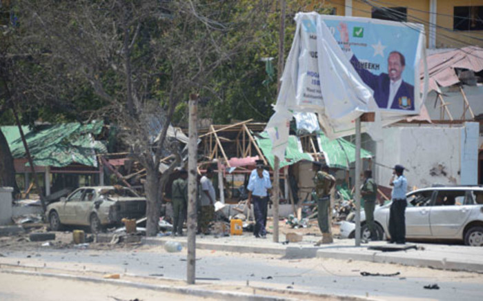 Security forces stand near a billboard depicting Somalian President Hassan Sheikh Mohamud, at the scene where two explosions occured in Mogadishu on 7 September 2013. Picture: AFP/ Mohamed Abdiwaha